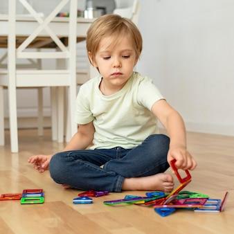 Netter junge, der mit spielzeug spielt