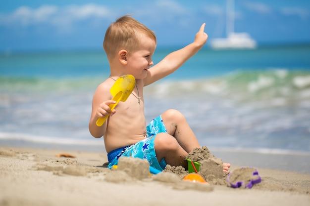 Netter junge, der mit strandspielzeug am tropischen strand spielt