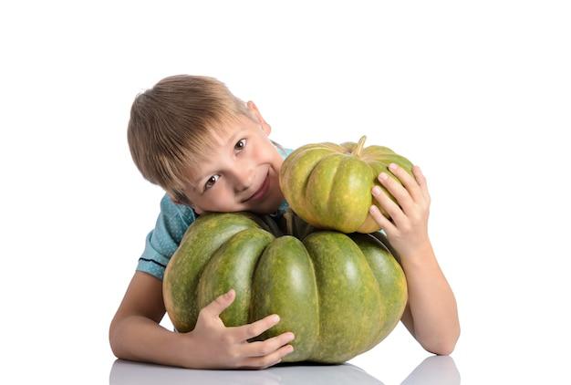 Netter junge, der mit verschiedenen kürbissen an halloween oder erntedankfest oder patch isoliert sitzt