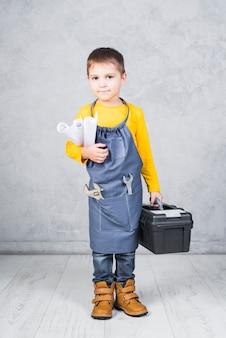Netter junge, der mit werkzeugkasten- und papierrollen steht