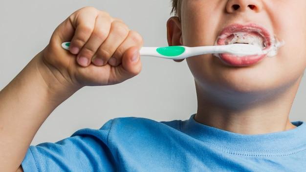 Netter junge der nahaufnahme, der zähne putzt