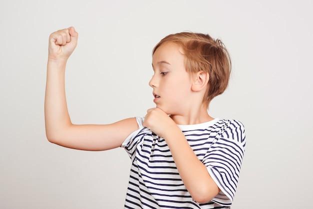 Netter junge, der seinen armmuskel zeigt. kindheit, fitness und sport. lustiges kind, das im studio aufwirft. erfolg, motivation und gewinnkonzept. schuljunge, der stärke und macht zeigt.