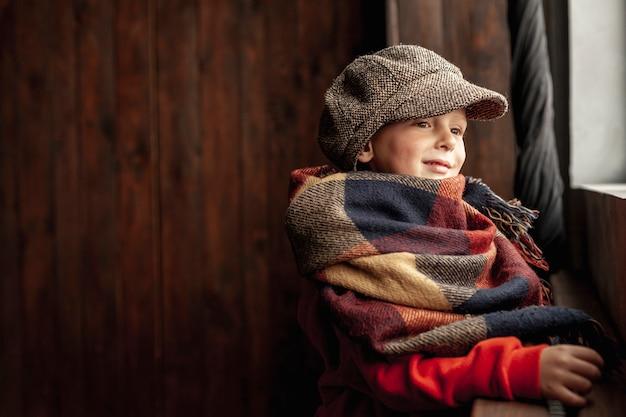 Netter junge der seitenansicht mit hut und schal