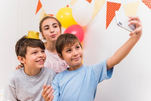 Netter junge, der selfie mit seinen freunden am intelligenten telefon nimmt