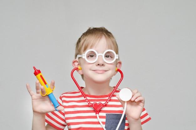 Netter junge, der spielt, um ein doktor zu sein