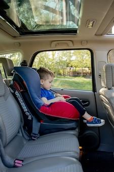 Netter junge der vorschule, der im sicherheitsautositz sitzt und während der familienreise mit dem auto weint