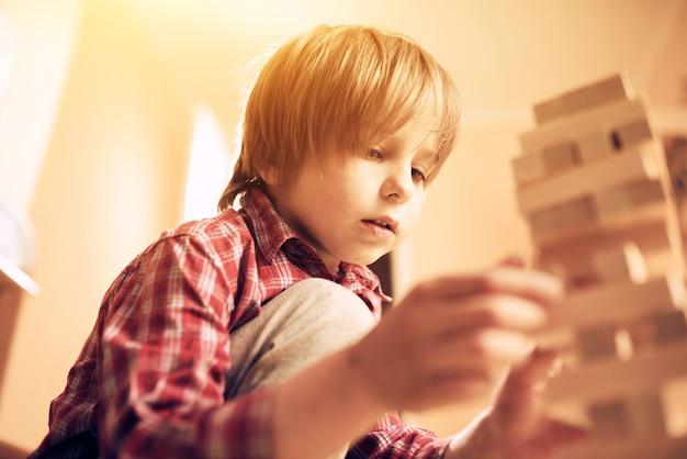 Netter junge der vorschule, der in einem tischspiel mit holzklötzen zu hause spielt