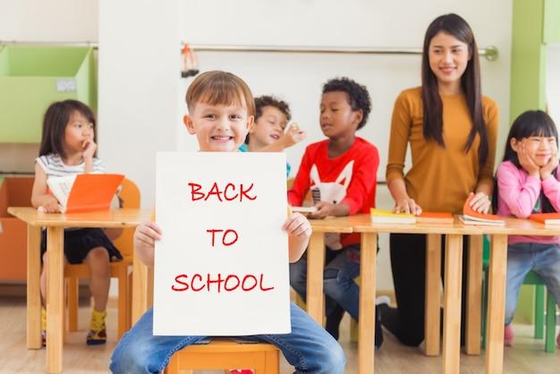 Netter junge, der zurück zu schuleplakat mit glücklichem gesicht im kindergartenklassenzimmer, kindergartenausbildungskonzept, weinleseeffektartabbildungen hält.