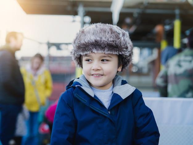 Netter junge des außenporträts mit lächelndem gesicht, kind, das draußen spielt