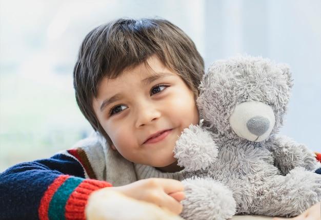 Netter junge des hohen schlüssellichtporträts, der seinen kopf auf teddybär legt und mit schönen braunen augen hinausschaut