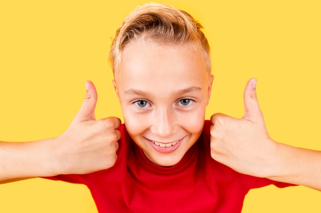 Netter junge des hohen winkels, der okayzeichen mit beiden händen zeigt