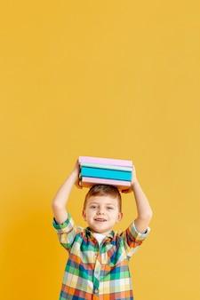 Netter junge des kopierraums mit büchern auf seinem kopf