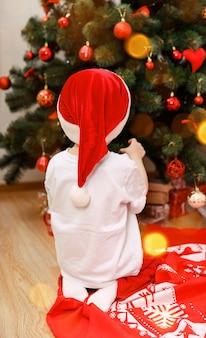 Netter junge drinnen in der nähe von weihnachtsbaum drinnen heiligabend-konzept
