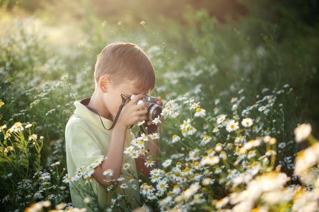 Netter junge fotograf schießt vor der kamera in der natur. kind macht ein foto im kamille blumenfeld.