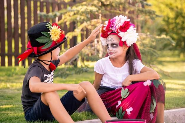 Netter junge im hut und im t-shirt, das blumenkranz auf kopf des hübschen mädchens mit gemaltem gesicht berührt, während beide sonnigen tag auf dem land genießen