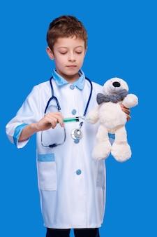 Netter junge im medizinischen mantel mit stethoskop, das teddybär im blauen isolierten hintergrund spritzeninjektion gibt