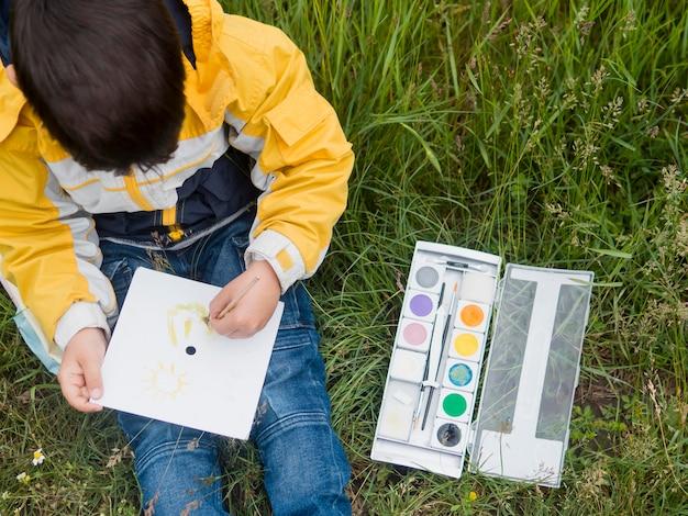 Netter junge im regenmantel, der draufsicht malt