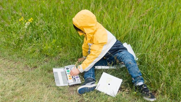 Netter junge im regenmantel, der lange ansicht malt