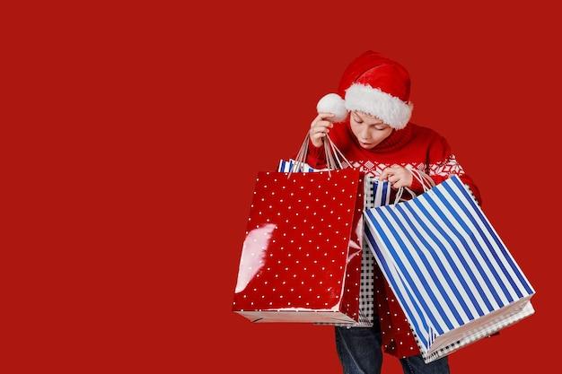 Netter junge im roten pullover, der einkaufstaschen hält