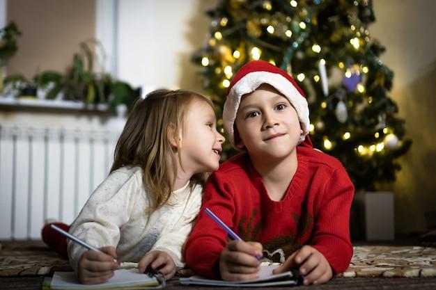 Netter junge im roten pullover und in der roten weihnachtsmütze schreibt einen brief an den weihnachtsmann