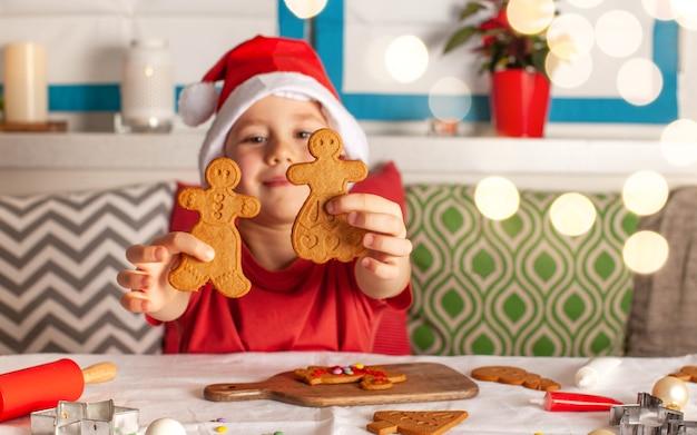 Netter junge im weihnachtsmann-hut macht lebkuchen am tisch weihnachtsbeleuchtung
