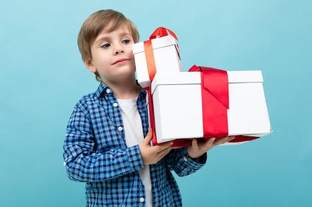 Netter junge in einem karierten hemd mit zwei geschenken seines schatzes auf einem hellblauen