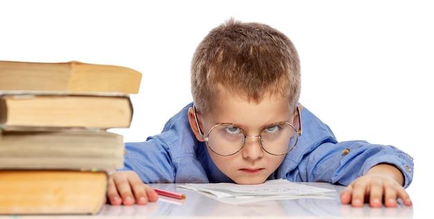 Netter junge in gläsern des schulpflichtigen alters ist vom lernen müde. ich hängte meinen kopf an lehrbücher. isoliert auf weißem hintergrund