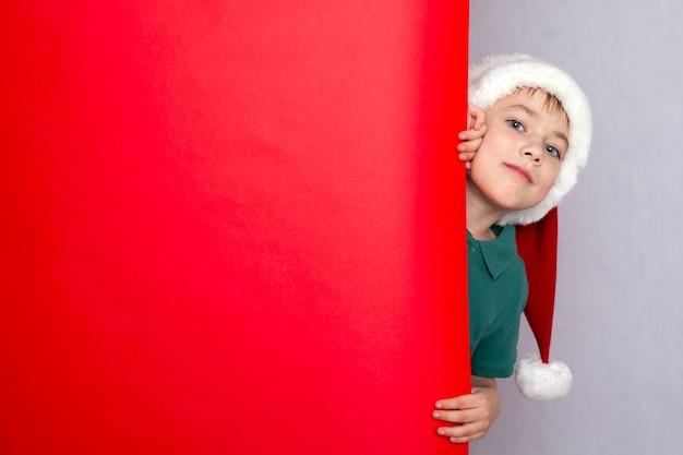 Netter junge in weihnachtsmann-mütze schauen rotes plakat der papierkarte lokalisiert über farbhintergrundraum für text. foto in hoher qualität