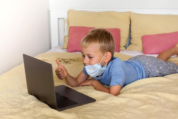 Netter junge kommuniziert über videolink unter verwendung eines laptops, der eine medizinische maske trägt