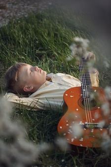 Netter junge liegt auf dem gras mit einer gitarre auf sonnenuntergang