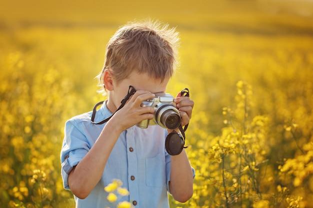 Netter junge macht fotos von blumen auf einem gelben feld im sommer