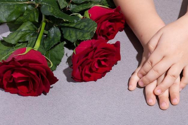 Netter junge mit blumenstrauß der schönen roten rosen auf tisch, draufsicht