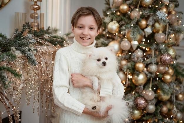 Netter junge mit einem hund in den armen in einem leichten pullover auf dem hintergrund eines weihnachtsbaumes