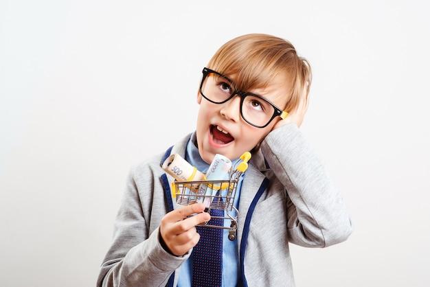 Netter junge mit einkaufswagen lokalisiert auf weiß. online shop. kleines kind, das einkaufswagen mit geld hält.