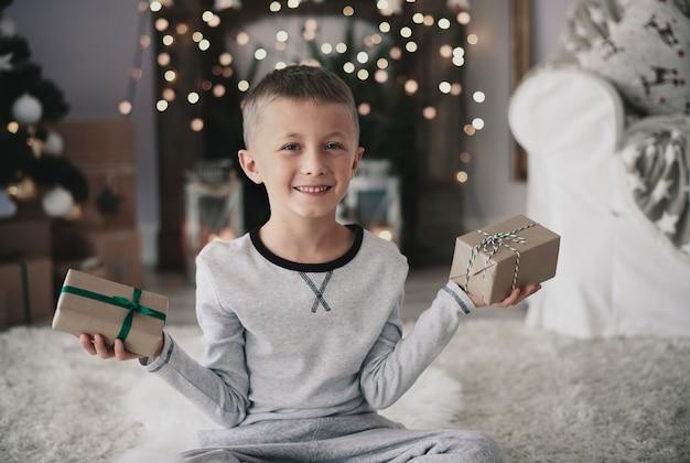 Netter junge mit geschenken, die kamera betrachten