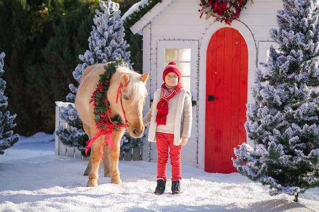 Netter junge mit gläsern und entzückendem pony mit festlichem kranz nahe dem kleinen holzhaus