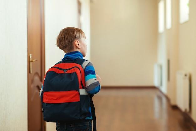 Netter junge mit rucksack, der zum unterricht geht. zurück zur schule. schüler mit rucksack in der schule, rückansicht.