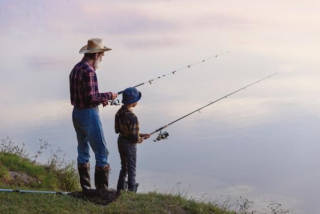 Netter junge mit seinem graubärtigen opa, der fisch auf dem see mit kescher bei sonnenuntergang fängt