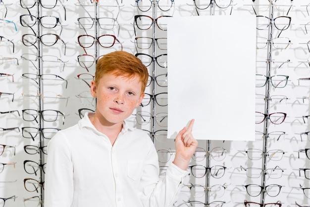 Netter junge mit sommersprosse auf gesicht zeigend auf schwarzes weißbuch im optikshop