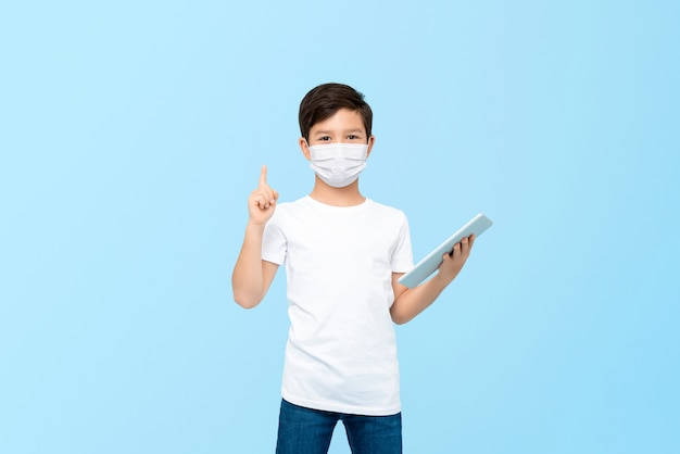 Netter junge mit tablet-computer, der medizinische maske trägt, um vor keimen und viren zu schützen