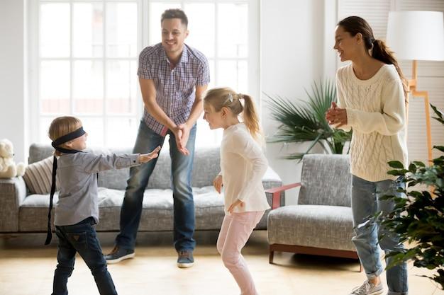 Netter junge mit verbundenen augen, der versteckenspiel mit familie spielt