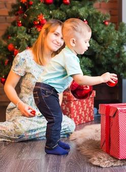Netter junge mit weihnachtskugeln
