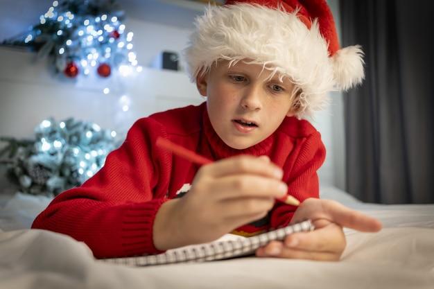 Netter junge schreibt brief an den weihnachtsmann, der sich auf das weihnachtswunder-wunschliste-kind-liegen vorbereitet