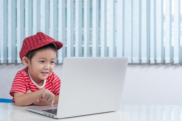 Netter junge spielt laptop im kinderzimmer