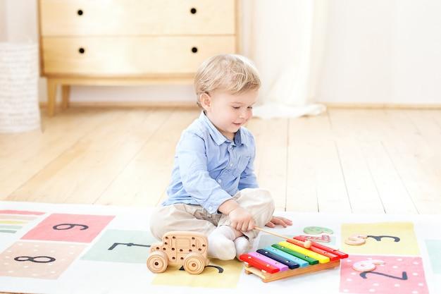 Netter junge spielt mit einem bunten musikinstrument des xylophons. lernspielzeug für kleine kinder. das konzept der kindheit und der kindlichen entwicklung. kind zu hause im kinderzimmer.