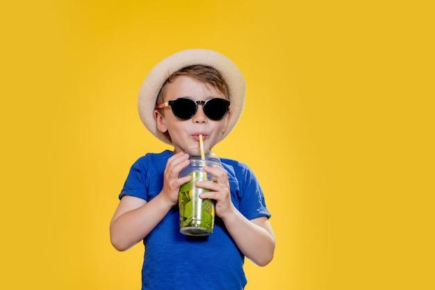 Netter junge trinken mojito-cocktail aus plastikbecher über gelbem studiohintergrund.