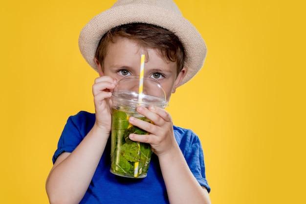 Netter junge trinkt mojito-cocktail aus plastikbecher über gelbem studiohintergrund