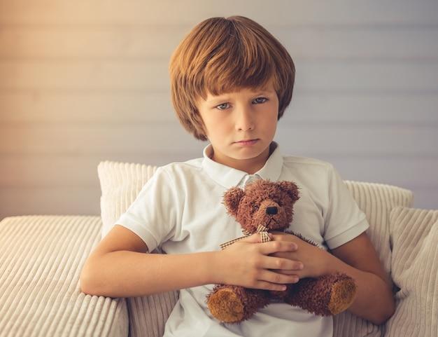 Netter junge umarmt einen teddybären und betrachtet kamera.