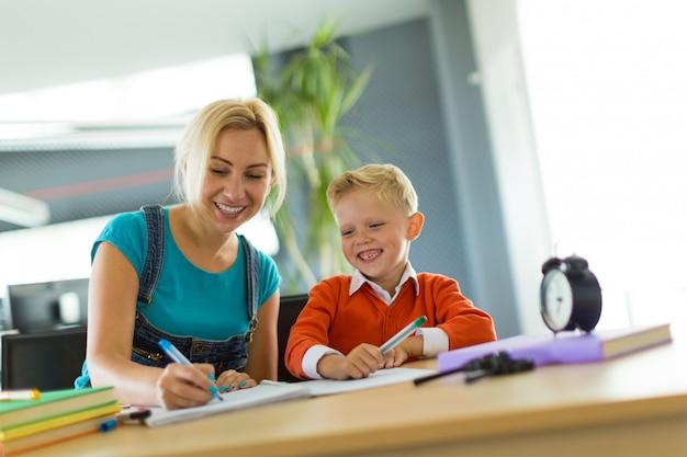 Netter junge und frau sitzen am schreibtisch im büro und zeichnen