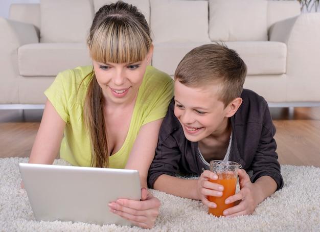 Netter junge und mutter, die auf boden unter verwendung der tablette liegt.